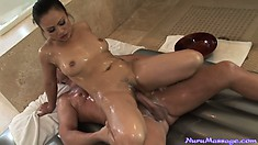 With both their bodies oiled up, her cunt slowly but steadily slips toward his cock