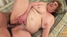 The fat mature lady has him pounding her hairy pussy all over the bed and loves it