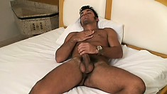 Roberto lies fully naked on the bed, massaging his body and stroking his cock