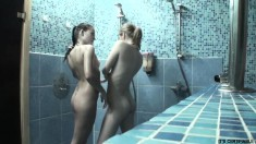 Two smoking hot babes play with each other while they take a shower