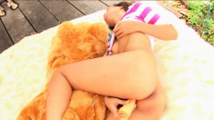 Hiroko rubs her nipples and drills her hairy cunt with a dildo outside