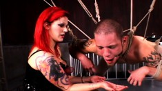 Blindfolded and gagged stud slave is suspended in bondage by fire-haired mistress