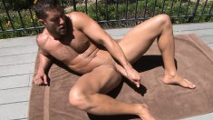 Ripped stud gets naked outdoors to wank his cock in the sun and finishes indoors