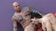 Inked Bald Stallion Gets His Huge Cock Sucked By A Skinny Young Dude